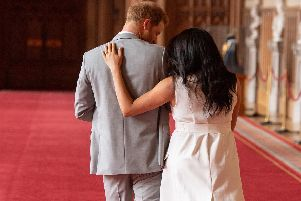 The Duke and Duchess of Sussex walk away with their baby son following a photocall at Windsor Castle.