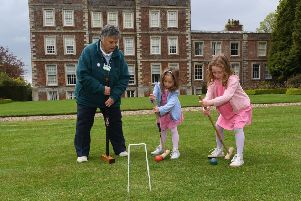 Glynis Docker demonstrating Garden Croquet to L-R Charlotte Berry 4 and Louisa Berry 5. EMN-190705-092544001