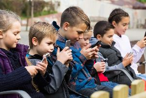 OBSESSED: Children glued to their phones