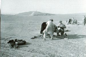Troops of the Westminster Regiment are pictured firing 2-pounder guns on the Shooter's Bottom Range. This picture is courtesy of the Canadian Department of National Defence SUS-191106-143912001