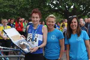 Nicky Thomas - of Portsmouth Joggers - was the first finisher for the host club. She picked up the club plate from race directors Rachel Thomas - centre - and Naouele McHugh - right. Picture: David Brawn