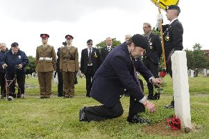 Soldiers from the Royal Hampshire Regiment and the Princess of Wales Royal Regiment have held a small service of remembrance at Milton Ceremony at the grave of L/CRP Leslie Webb who was killed on D Day.'Former soldier Keith Unwin lays a rose.'Picture: Ian Hargreaves  (140619-7)