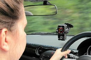 Ban on drivers using hands-free phones in cars should be considered, according to MPs