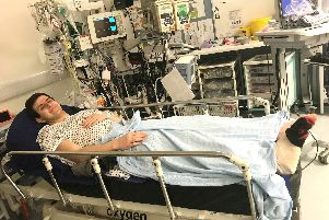 Aidan Lamer in a hospital bed bed after nearly losing his leg in a motorcycle accident.