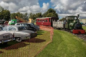 A display of vintage cars at the Classic Wheels event in the Skegness Water Leisure Park in 2017, with Jurassic and historic railway carriages steaming past.