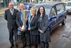 Neil Greese from the Pompey Hearse Ltd, John Mitchell from Portsmouth Football Club, staff Christine Kearns and Emma Neale, with the EFL Trophy and the Pompey Hearse outside their shop in London Road, North End, Portsmouth.'Picture: Habibur Rahman
