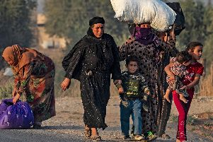 Syrian Arab and Kurdish civilians flee amid Turkish bombardment on Syria's northeastern town of Ras al-Ain in the Hasakeh province along the Turkish border on October 9, 2019.  Photo: Delil SouleimanAFP via Getty Images