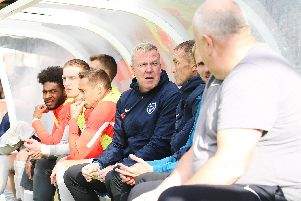 Pompey boss Kenny Jackett, centre, in the visitors' dugout at Kingsmeadow   Picture: Joe Pepler