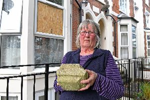 Pictured is Sue Forrest holding the large piece of masonry that was thrown through her flat window.'Picture: Malcolm Wells (191016-8473)