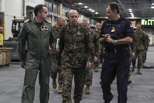 General David H Berger, centre, the 38th Commandant of the United States Marine Corps, is shown on board HMS Queen Elizabeth this week. He got to see US F-35 jets fly from the carrier's decks as part of its Westlant 19 deployment. Picture: HMS Queen Elizabeth on Twitter (@HMSQNLZ)