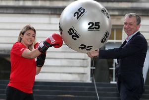 Paul Mullan, chair of the Northern Ireland National Lottery Distributors Forum, with National Lottery-funded youth worker Amy Stewart, from Monkstown Boxing Club, celebrate 25 knockout years of The National Lottery.