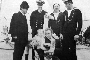 Three-year-old Stephen Bridgeland found himself the centre of attention when he boarded HMS Abdiel. Stephen is seen with his father, Leading Seaman David Bridgeland. Watching are, from left: navy minister Frank Judd, Commander D Husband, Leading Seaman Bill Cunningham and Able Seaman Stan Stanley.
