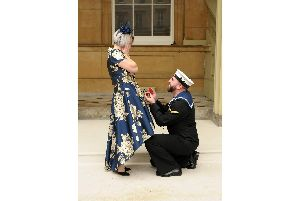 Air Engineering Technician Matthew Gallimore, Royal Navy, goes down on one knee to propose to his girlfriend Adele Thomasson in the Quadrangle of Buckingham Palace, in London, after he received his MBE from the Duke of Cambridge. Photo: Fiona Stapley-Harding/PA Wire