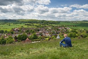 A youth sitting on Park Hill overlooking East Meon in the Meon Valley Picture: Shutterstock