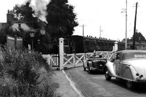THEN: A train for Havant departs Langstone Halt and crosses Langstone Road level crossing. Picture: Barry Cox collection.