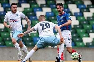 Linfield's Josh Robinson clears the danger at Windsor Park