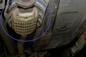 Circled: A catalytic converter in place on the underside of a car.
