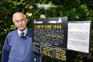 John Gerken with his memorial sign commemorating five American men who lost their lives 750 feet from his house on D-Day 1944
