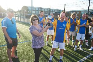 Catherine Smith presents the winning trophy for the Soccer 8s charity football tournament to her son, Carl Smith, who played on the winning team - Real Sociable'(Photo by Ben Duffy)