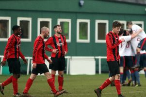 The Whitworth players look dejected while ON Chenecks celebrate one of their goals in the background. Chenecks claimed a 7-0 success in the United Counties League Premier Division clash. Pictures by Alison Bagley