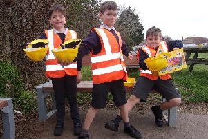 Children from the school wearing the high-vis jackets and hard hats and proudly showing the lego that was donated by Mackley