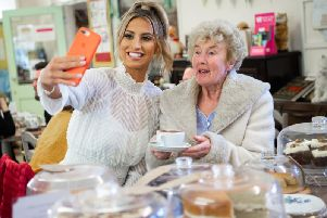 Ferne McCann takes a selfie with Shirley Margaret Hill, at a Royal Voluntary Service Centre in Lancing. Photo: Matt Crossick/PA Wire