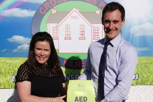 Mr Mullan taking receipt of the AED from Mrs Brenda Turner, daughter of Francis McWilliams