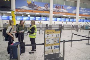 Katie O' Mara (left) and Maddison Millar (centre) talk to a government member of staff in front of empty Thomas Cook check-in desks at Gatwick Airport in Sussex. Photo: Steve Parsons/PA Wire