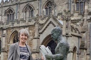 Wilkin Chapman Partner Flora Bennett outside the beautiful St James'Church, Louth with the towns Meridian Line Man  a popular draw for visitors.