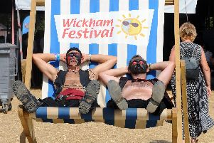 Festival goers relax on the big deckchair at Wickham Festival. Picture: Sarah Standing (180618-3380)
