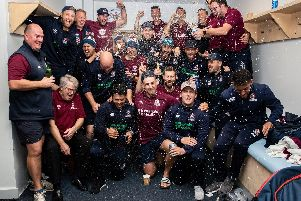 The Northants players and staff celebrate promotion at Bristol on Thursday morning