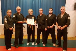 Emma Morley is pictured with Cobra Ju-Jitsu senior sensei Nick Preston, watched by Cobra dan grades.