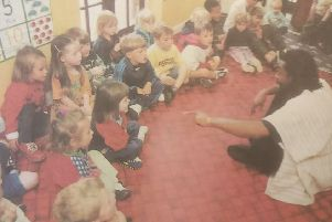 Winston Nzinga sits with the children as he tells them one of his stories