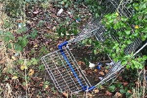 A ditched shopping trolley on the railway embankment beside galley Hill bridge in Sleaford which reveals layers of litter built up beneath.