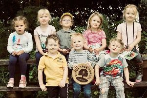 Youngsters from Busy Bees Early Years and nature Centre, with their gold award plaque from the Woodland Trust.