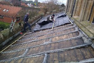 Plastic sheeting being nailed on to the stripped south aisle roof of Billingborough Church, by churchwarden Geoff Hallam (left) and parochial church council member Trevor Wells. EMN-190612-180349001