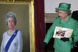 Queen Elizabeth II unveils a portrait of herself by artist Theodore Ramos at the Guildhall in Windsor, 03 June 2002, to mark her Golden Jubilee. A 1954 painting of the Queen hangs on the wall in the background.   (Photo credit should read MARTIN HAYHOW/AFP/Getty Images)