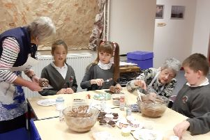 Sleaford Lionesses helping children decorate cakes. EMN-191217-124230001