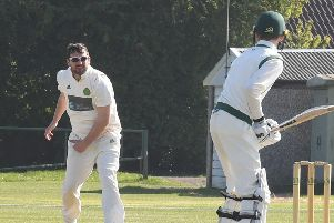 Tom Baxter sends down a delivery.