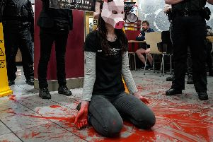 A protester surrounded by fake blood in McDonald's