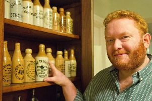 Neil Reid with some of the stoneware bottles in his collection