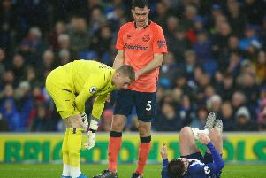 Brighton striker Aaron Connolly is on the floor after contact from Everton defender Michael Keane