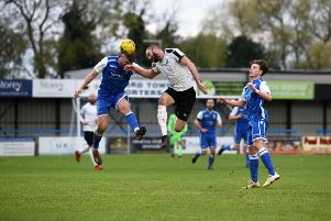 Daventry Town's Adam Confue goes for a header at Bedford Town. Photo: June Essex