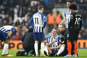 Brighton defender Dan Burn receives treatment after a collision with Chelsea's Reece James