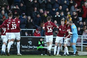 Cobblers players run over to celebrate with Paul Anderson after the midfielder's opening goal against Morecambe. Pictures: Pete Norton