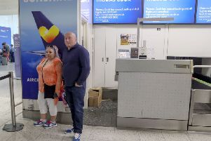 Martin Nowell and Pixie Flageul in front of empty Thomas Cook check-in desks at Gatwick Airport in Sussex. Photo: Steve Parsons/PA Wire