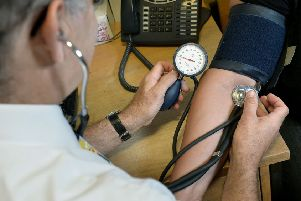 File photo dated 10/09/14 of a doctor checking a patient's blood pressure. Photo credit: Anthony Devlin/PA Wire