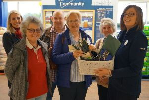 Tesco store's Katie Hubbert hands over the gardening goodies to representatives of Greenacres EMN-191106-114524001