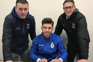 Evan Moran (centre) signs at Dungannon Swifts as club chairman Keith Boyd (left) and manager Kris Lindsay look on. Pic courtesy of Dungannon Swifts.