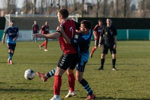 Jack Breed - in blue - battles for the ball in Portchester's visit to Fareham last season